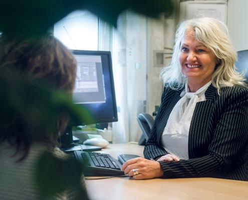 Mariann Thiesen smiler paa kontoret