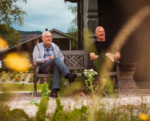 Egil Skogestad og Ånen Werdal sitter på en benk ved Lygnevann og smiler